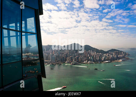 Horizontal view of a tourist taking photos from the Sky100 observation deck at the International Commerce Centre - Stock Photo