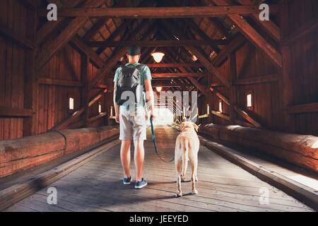 Young tourist with his dog inside of the covered bridge over the river in Radosov, Czech Republic - Stock Photo