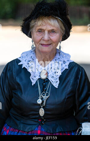 Portrait of senior lady, 60, facing, smiling. Dressed in Victorian costume, and black hat. Eye-contact. - Stock Photo