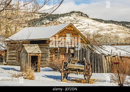 Log home, outhouse, and a wagon on a winter day in a ghost town with a bit of blue sky and sunlight - Stock Photo