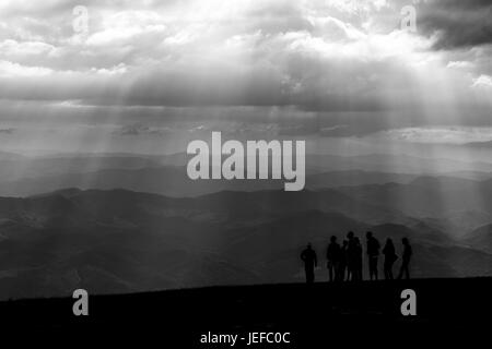 Some people on top of a mountain, with other mountains and hills in the background, and sunrays coming out of the - Stock Photo