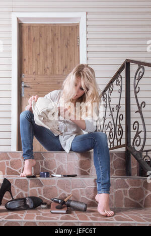 Girl sitting in front of a locked front door Stock Photo ...