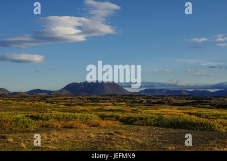 Moss covered lava field and volcano mount near lake Myvatn summer landscape, Iceland - Stock Photo