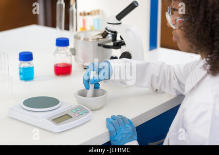 Female Scientist Using Mortar Working In Laboratory Making Chemicals Powder For Experiment, Researcher Mix Race - Stock Photo