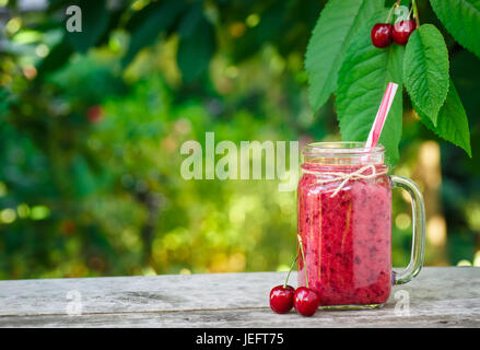 cherry smoothie in mason jar and fresh ripe cherries on wooden table with garden on the background. Healthy summer - Stock Photo