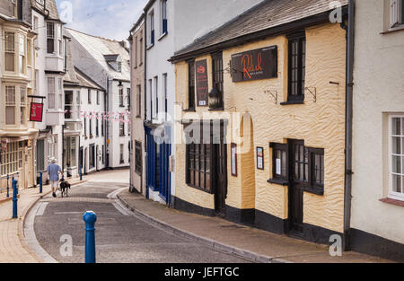 14 June 2017: Ilfracombe, North Devon, England, UK - A man walks with his greyhound down Fore Street, formerly the - Stock Photo