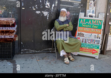 An older Islamic merchant rests while watching his stand on 37th Avenue in Jackson Heights, Queens, New York - Stock Photo