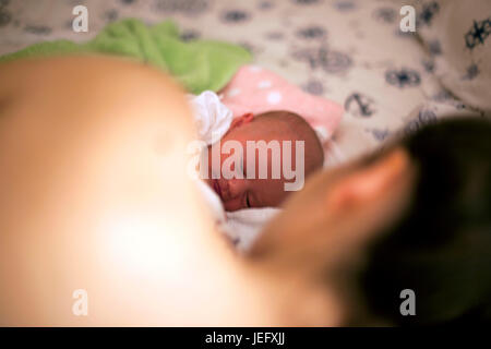 Sleeping newborn baby in mother embrace - Stock Photo