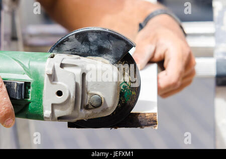 Close-up a man with electric jig cutting wooden board - Stock Photo