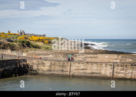 View of Dunstanburgh Castle from Craster Harbour, Northumberland, England, UK, Europe. - Stock Photo