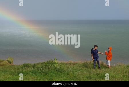 Two Boys On Top of Langstone Rock with a Rainbow Over the English Channel. Dawlish, Devon, UK. June, 2017. - Stock Photo