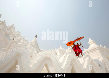 Monks with umbrella in Hsinbyume Pagoda Temple in Mandalay Myanmar Mingon Sagaing region White temple pagoda Myanmar - Stock Photo
