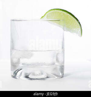 close up of a short glass with a clear liquid and a green lime on the rim isolated on a white background - Stock Photo