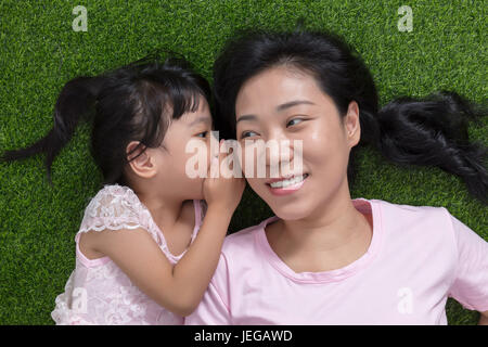 Asian Chinese mother and daughter lying on the grass whispering and gossiping at outdoor park - Stock Photo