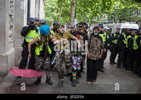 London, UK. 24th June, 2017. Clowns perform in front of police lines among anti-fascist counter-protesters protesting - Stock Photo