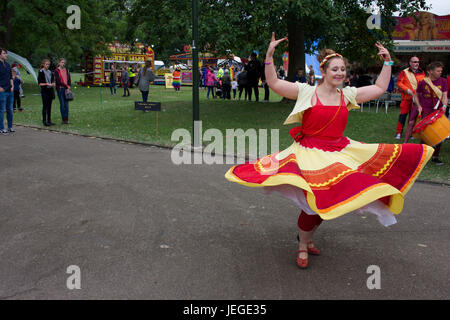 Young woman dressed in flamenco style waving red and yellow dress dancing on LGBT pride event in Hanley park,Stoke - Stock Photo