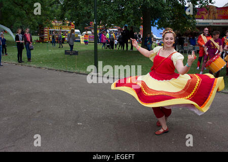 Woman wearing red and yellow flamenco style,waving dress dancing on LGBT pride event in Hanley park,Stoke on Trent,Staffordshire,United - Stock Photo