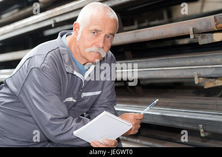 man in metal industry warehouse checking products - Stock Photo