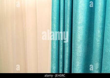 Bright blue curtain with beige wall in background - Stock Photo