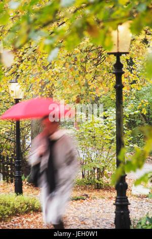 Mann, mittleren Alters mit Regenschirm bei Laterne, Bewegungsunschärfe | middleaged man with an umbrella next to - Stock Photo