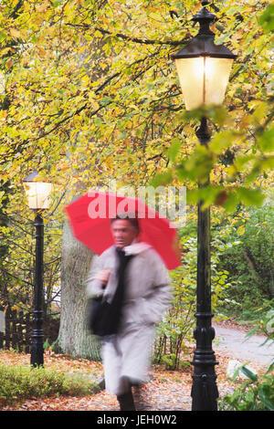 Mann, mittleren Alters mit Regenschirm bei Straßenlaterne, Bewegungsunschärfe | middleaged man with an umbrella - Stock Photo