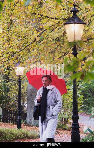 Mann, mittleren Alters mit Regenschirm bei Straßenlaterne | middleaged man with an umbrella next to a street lamp - Stock Photo