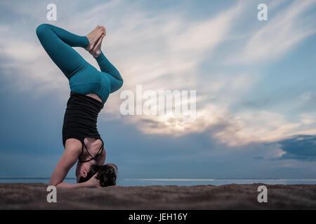 Full length shot of young woman practicing sirsasana. - Stock Photo