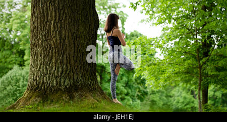 Attractive young female is practicing yoga and doing asana Vrikshasana in the morning. - Stock Photo