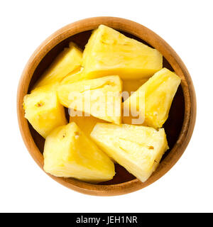 Pineapple pieces in wooden bowl. Ananas comosus, the edible multiple fruit of a tropical plant, consisting of coalesced - Stock Photo