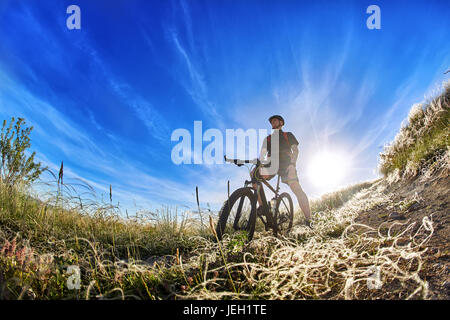 Low angle view of cyclist standing with mountain bike on trail at sunrise. - Stock Photo