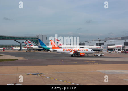 Civil aviation. London Gatwick Airport, UK, with planes at their gates and an easyJet Airbus A319 in the foreground - Stock Photo