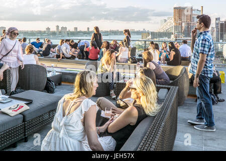 looking North over Ink48 Hotel rooftop bar Press Lounge at sunset with young people socializing chatting & looking - Stock Photo
