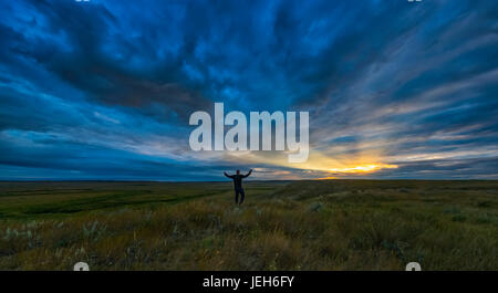 Man standing with his arms spread open at daybreak in Grasslands National Park; Saskatchewan, Canada - Stock Photo