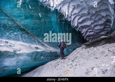 A man explores a tunnel beneath the ice of Canwell Glacier in the Alaska Range in winter; Alaska, United States - Stock Photo