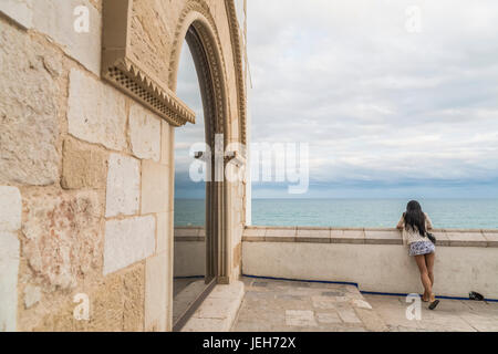 A young woman looks out over a wall to the ocean at Maricel Palace; Sitges, Barcelona province, Spain - Stock Photo