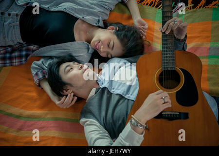 couples of asian younger man and woman playing guitar with relaxing and happiness emotion - Stock Photo