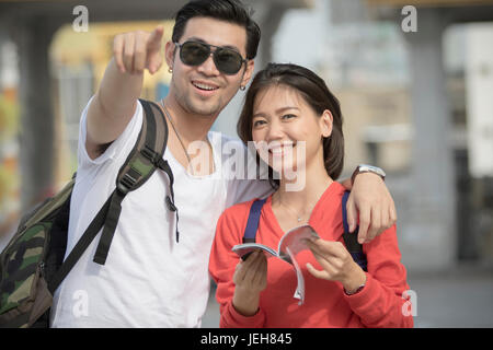 asian younger backpack man and woman happy traveling destination - Stock Photo