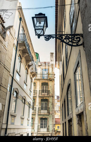 Narrow street lined with buildings; Lisbon, Portugal - Stock Photo