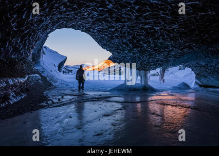A man walks out the entrance of an ice tunnel at the terminus of Canwell Glacier in the Alaska Range in mid-winter; Alaska, United States of America