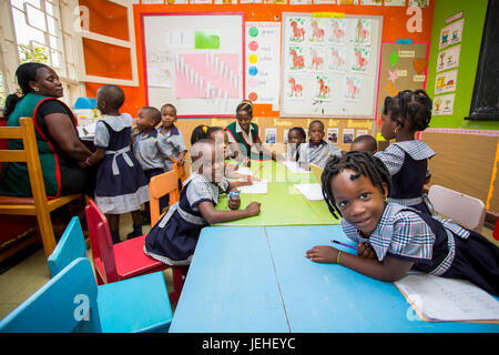 Young children in a classroom with a teacher at the Treasures Christian Preschool; Kampala, Uganda - Stock Photo