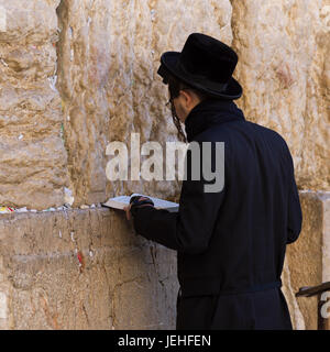 An orthodox jew standing at the Wailing Wall, old city of Jerusalem; Jerusalem, Israel - Stock Photo