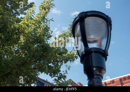 Directly Below Shot Of Street Light Against Sky trees and build roof edging - Stock Photo