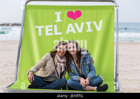 A mother and daughter sit together in a large chair on the beach which says I love Tel Aviv; Tel Aviv, Israel - Stock Photo