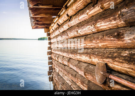 Wall of log house on the river bank close-up with a beautiful landscape in the background. - Stock Photo