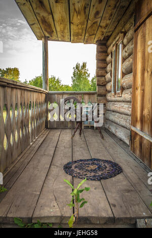 Old sewing spindle is standing on the terrace of an old wooden house. - Stock Photo