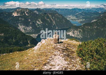 Young man sitting on the edge of mountain and enjoying spectacular view. Vintage toned image - Stock Photo