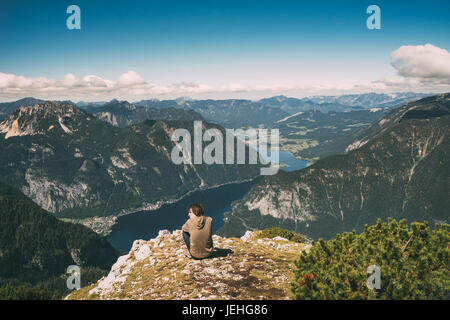 Young man relaxing on the edge of mountain and enjoying wonderful view. Vintage toned image - Stock Photo