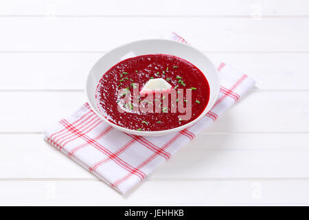 plate of beetroot cream soup on checkered dishtowel - Stock Photo