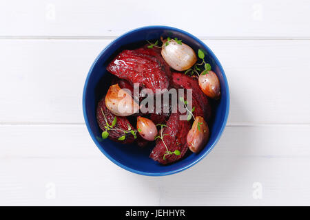 bowl of baked beetroot with garlic and thyme on white wooden background - Stock Photo