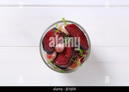 glass of baked beetroot with garlic and thyme on white wooden background - Stock Photo